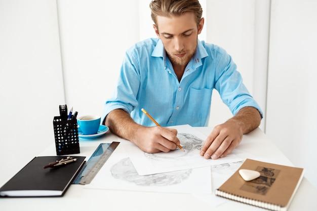 Hombre de negocios pensativo confiado hermoso joven que trabaja sentado en el dibujo de la tabla en libreta. interior de oficina moderno blanco.