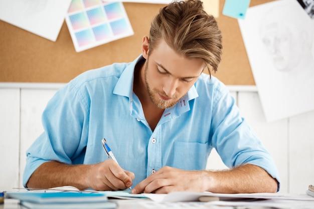 Hombre de negocios pensativo confiado hermoso joven que trabaja sentado en la escritura de la tabla en la libreta. interior de oficina moderno blanco