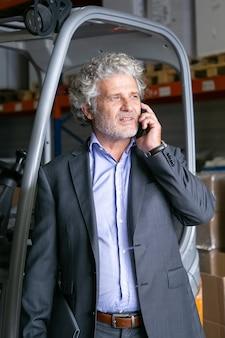 Hombre de negocios pensativo de pie en el almacén cerca de la carretilla elevadora y hablando por teléfono celular