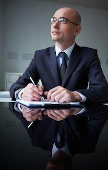 Hombre de negocios pensativo con un sujetapapeles