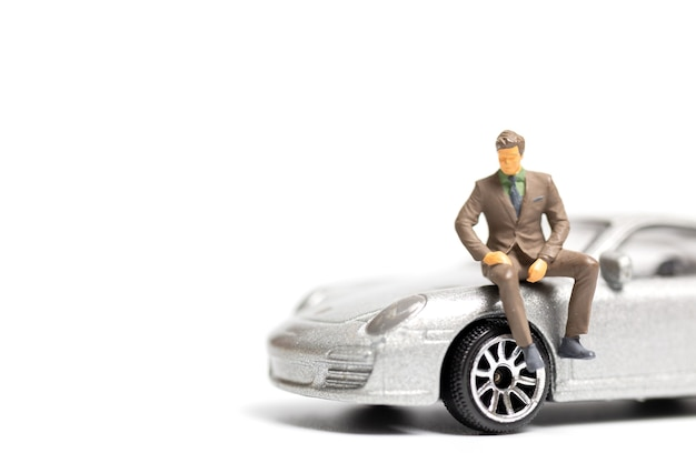 Hombre de negocios de personas en miniatura sentado en un coche y copia espacio para texto