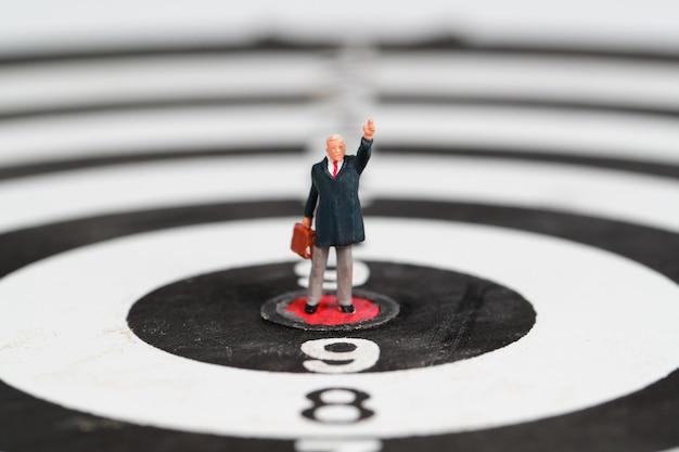 Hombre de negocios de pie en la diana de centro idea objetivo del objetivo financiero y de negocios