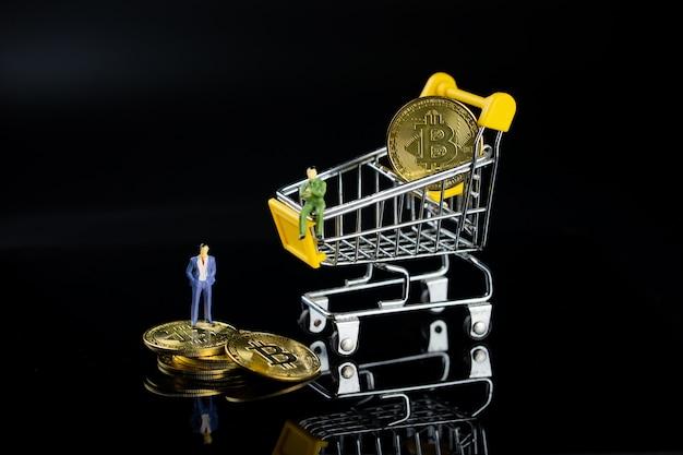 Un hombre de negocios está de pie sobre las monedas de oro, y otro está sentado en un carrito de compras.