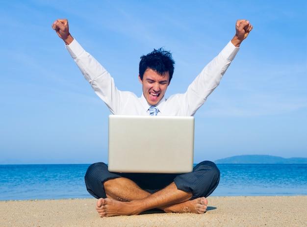Hombre de negocios en la playa con la computadora portátil