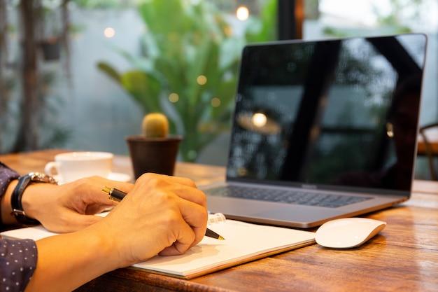 Hombre de negocios con la pluma que escribe la nota en el cuaderno con el ordenador portátil en