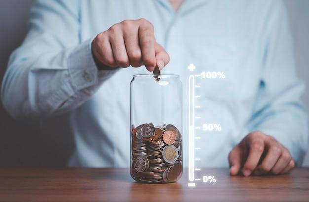 Hombre de negocios poniendo monedas al tarro de ahorro de dinero con escala virtual de cantidad de ahorro para el futuro.