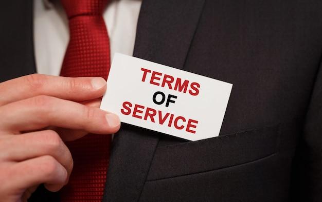 Hombre de negocios poniendo una tarjeta con los términos de servicio de texto en el bolsillo