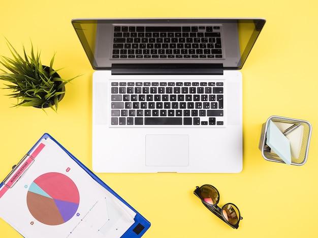 Hombre de negocios portátil en el concepto de vista superior de escritorio amarillo, auriculares, maceta de hierba, gafas de sol