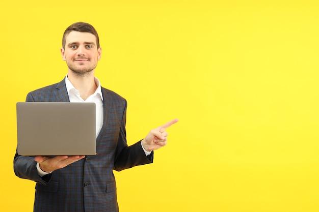 Hombre de negocios con portátil sobre fondo amarillo, espacio para texto.