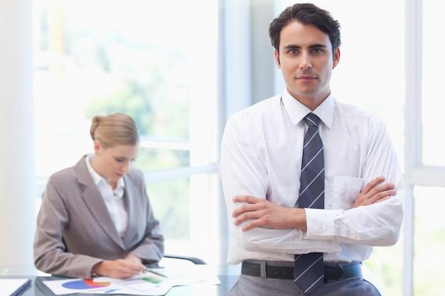 Hombre de negocios posando mientras su colega está trabajando