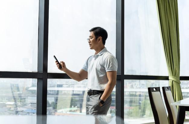Hombre de negocios, posición, en, edificio de oficinas, ventana, mirar teléfono celular