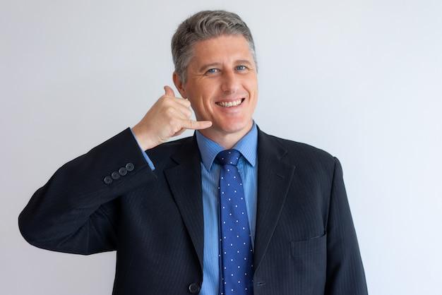 El hombre de negocios positivo que gesticula me llama