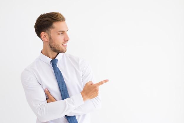 Hombre de negocios positivo que señala el dedo a un lado