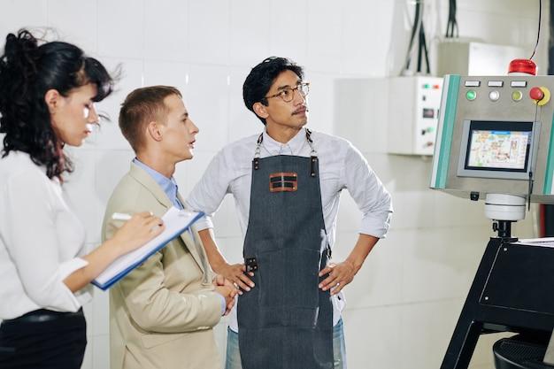 Hombre de negocios preguntando a trabajador tostador de café acerca de la nueva máquina tostadora moderna