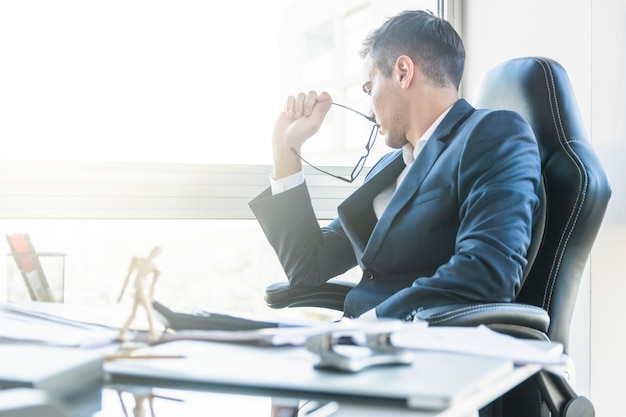 Hombre de negocios preocupado que se sienta en silla con el escritorio de oficina abarrotado
