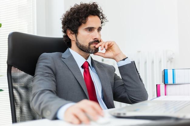 Hombre de negocios preocupado que trabaja en su computadora portátil