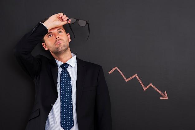 Hombre de negocios preocupado con signo de disminución de beneficios