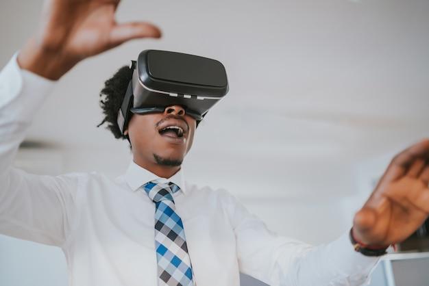 Hombre de negocios profesional con casco de realidad virtual en un descanso del trabajo en la oficina moderna. concepto de negocio y tecnología.