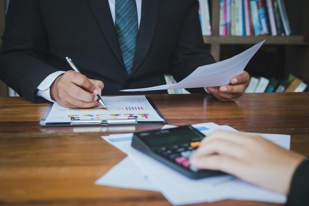 Hombre de negocios que analiza negocio creciente en gráfico de negocio en sus manos.