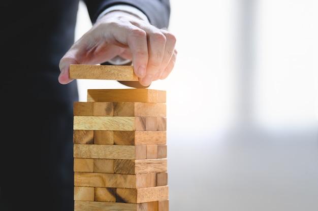 Hombre de negocios que arregla el bloque de madera y que apila como torre a mano.