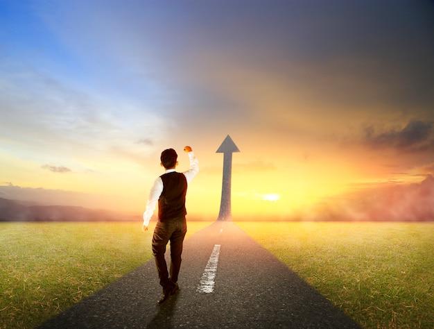 Hombre de negocios que camina en la carretera que sube como una flecha para el éxito
