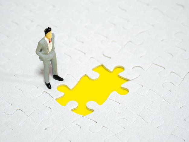 Hombre de negocios que se coloca delante del rompecabezas que falta del pedazo en el fondo amarillo.