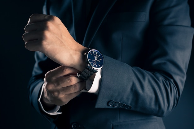 Hombre de negocios que comprueba tiempo del reloj