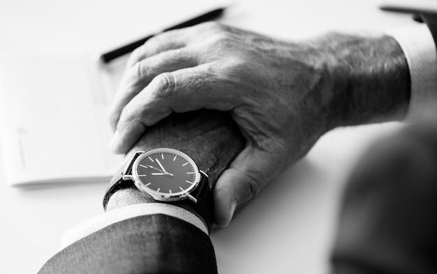 Hombre de negocios que controla tiempo en reloj de mano