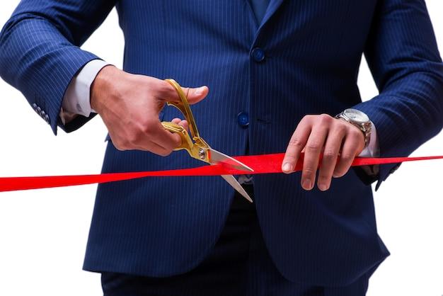 Hombre de negocios que corta la cinta roja aislada en blanco