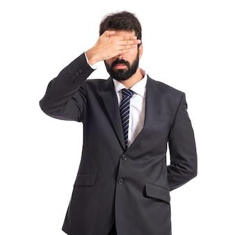 Hombre de negocios que cubre sus ojos sobre fondo blanco aislado