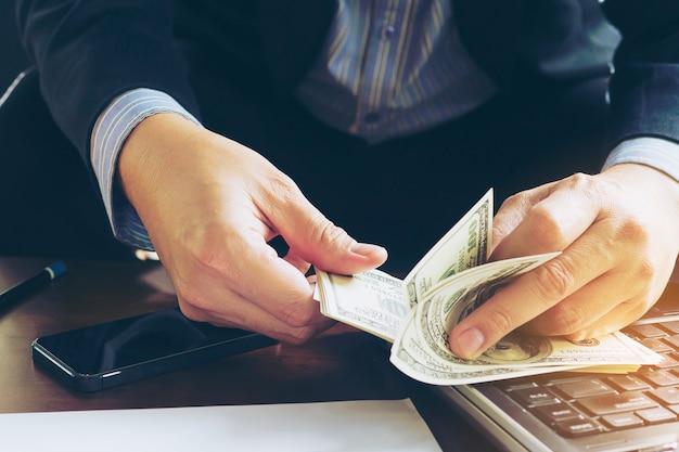 Hombre de negocios que cuenta el billete de banco del dólar - concepto en línea del negocio