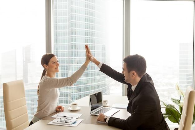 Hombre de negocios que da a empresaria el alto cinco en la oficina