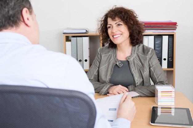 Hombre de negocios que entrevista al candidato femenino para el trabajo en oficina.