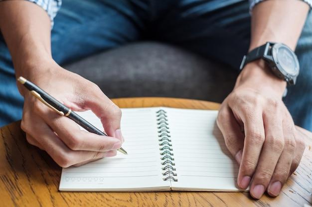 Hombre de negocios que escribe algo en el cuaderno en oficina