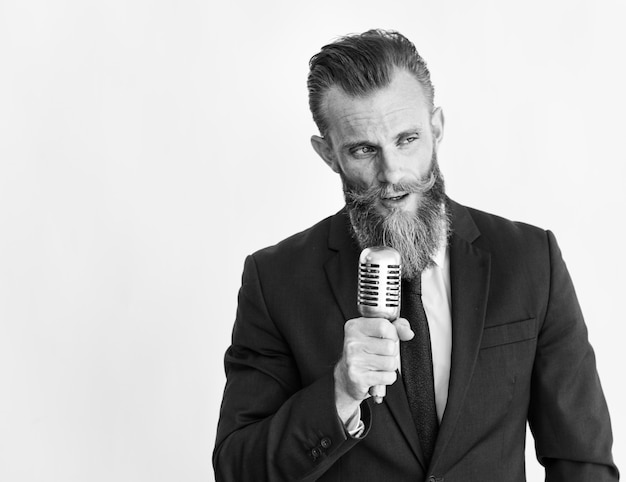 Hombre de negocios que habla en el micrófono en escala de grises