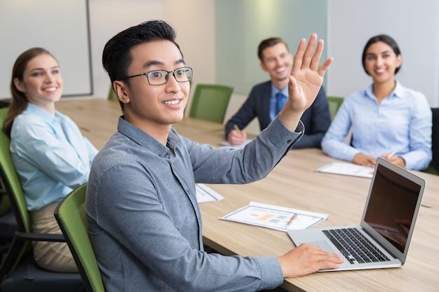 Hombre de negocios que levanta la mano en la conferencia de la sonrisa
