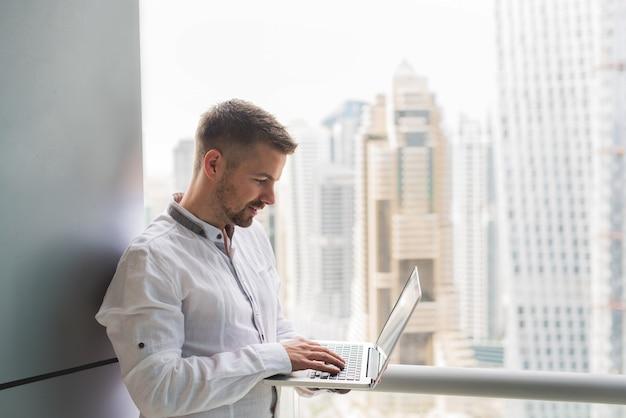 Hombre de negocios que lleva a cabo el funcionamiento del balcón de la oficina del ordenador portátil. impresionante vista de la ciudad scape office.