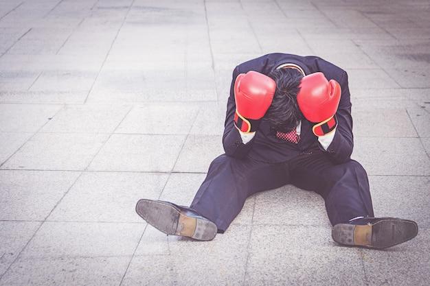 Hombre de negocios que lleva el guante de boxeo rojo que se sienta en el piso pero que siente la tensión sobre trabajo.