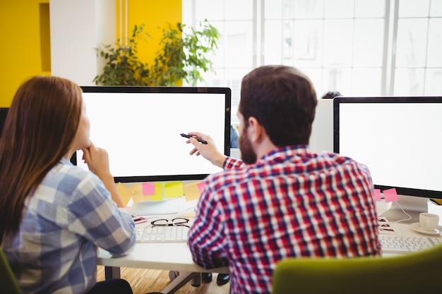 Hombre de negocios que muestra algo al compañero de trabajo femenino en la computadora