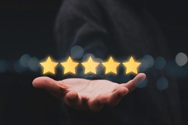 Hombre de negocios que muestra cinco estrellas a mano para el resultado de la evaluación del cliente.