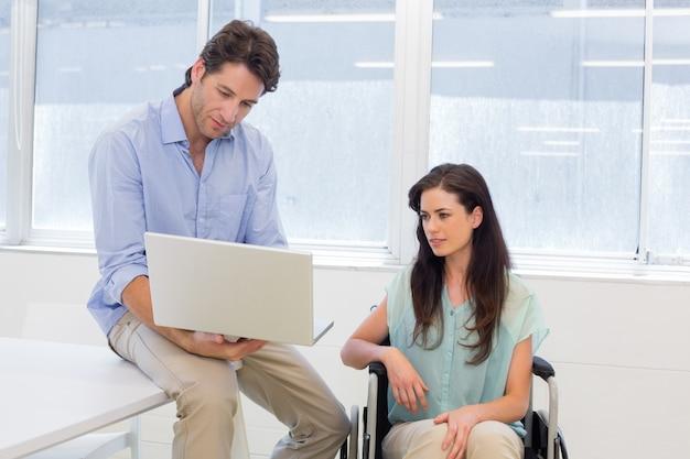Hombre de negocios que muestra a la mujer en silla de ruedas la computadora portátil