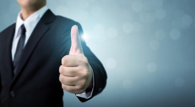El hombre de negocios que muestra muy bien o mano firman pulgar