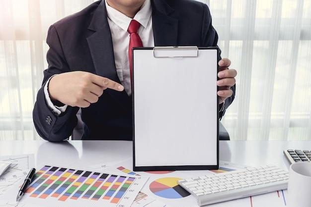 Hombre de negocios que muestra un papel en blanco en la oficina con computadora de escritorio y documentos