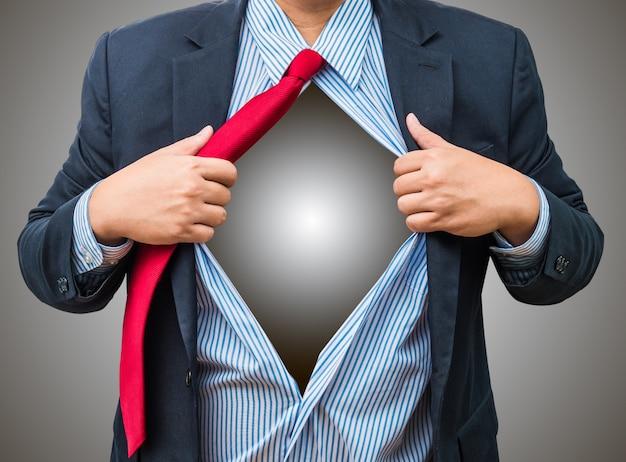 Hombre de negocios que muestra un traje de superhéroe debajo de su traje, aislado sobre fondo blanco