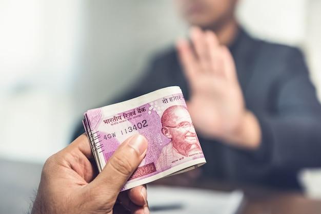 Hombre de negocios que ofrece dinero en forma de moneda rupia india