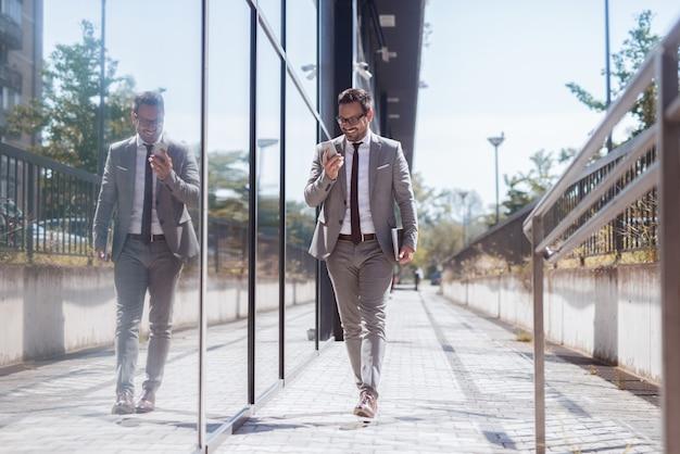 El hombre de negocios que pasa por windows agrega usando el teléfono inteligente para leer / escribir mensajes de texto. en otra mano tableta.