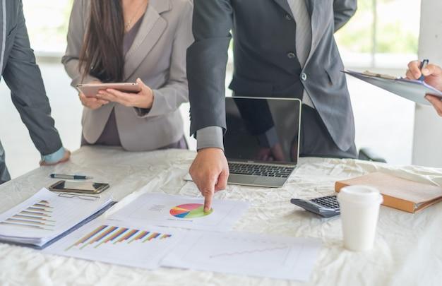 Un hombre de negocios que planifica el negocio y analiza muchos gráficos gráficos