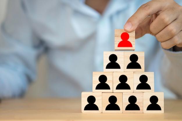 Hombre de negocios que pone la ilustración roja que imprimió el icono humano rojo de la pantalla a la parte superior del icono humano negro. concepto de nave líder y trabajo en equipo.