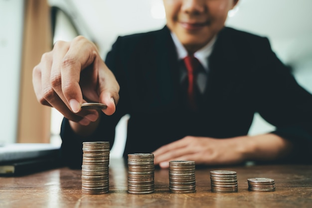 Hombre de negocios que pone la pila de la moneda intensifica el aumento ahorra el dinero