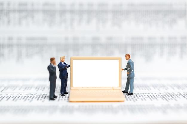 Hombre de negocios que presenta en la computadora portátil de la pantalla blanca
